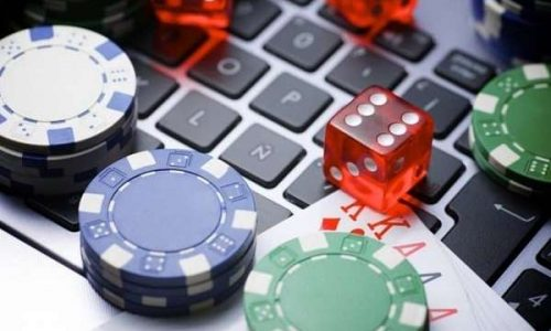 poker chips, dice, and cards on a laptop computer keyboard signifying online gambling